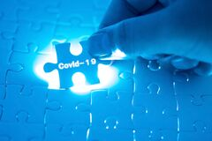 Doctor`s hand holding a jigsaw puzzle with Covid-19 words. Health concept. Stop Novel Coronavirus outbreak covid-19 2019-nCoV
