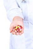 Doctor's hand holding many yellow tablets Stock Photography