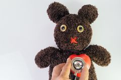 Doctor`s hand holding stethoscope put on red heart on cute brown handmade fluffy doll with pitty eyes, healthcare for children or royalty free stock image