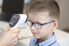 Doctor`s hand measures the temperature of the boy in a blue shirt and glasses using an electronic infrared thermometer. royalty free stock photography