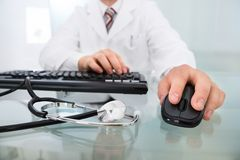 Doctor's hand on mouse and keyboard Royalty Free Stock Photography