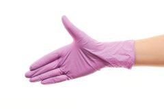 Doctor's hand in purple sterilized surgical glove giving for handshake. Close up of female doctor's hand in purple sterilized surgical glove giving for handshake Royalty Free Stock Photography
