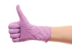 Doctor's hand in purple surgical glove showing thumbs up sign. Close up of female doctor's hand in purple sterilized surgical glove showing thumbs up sign Stock Image