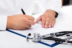 Doctor`s hand signing document. With stethoscope on desk stock photography