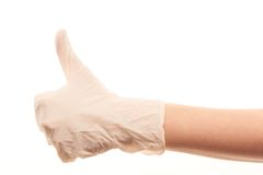 Doctor's hand in white surgical glove showing thumbs up sign. Close up of female doctor's hand in white sterilized surgical glove showing thumbs up sign against Royalty Free Stock Photo
