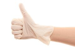 Doctor's hand in white surgical glove showing thumbs up sign. Close up of female doctor's hand in white sterilized surgical glove showing thumbs up sign against Stock Photos