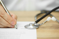 Doctor's hand  is writing prescription for patient diagnose Stock Images