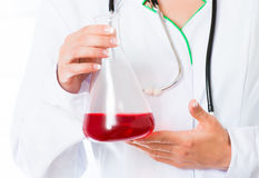 Doctor's hands with flask Stock Photos
