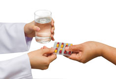 Doctor's hands giving  pills and glass of water to patient's han Stock Images