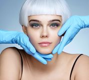 Doctor`s hands in gloves touching face of beautiful woman royalty free stock photo