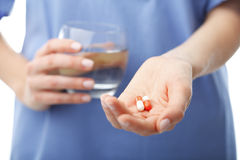 Doctor's hands holding two pills and a glass of water Royalty Free Stock Image