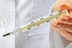 Doctor's hands showing thermometer Stock Photos