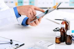 Doctor`s hands working on a digital tablet at his Office. Close up of Doctor`s hands working on a digital tablet at his Office. Health care, Medical and Pharmacy Stock Image