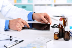 Doctor`s hands working on a digital tablet at his Office. Close up of Doctor`s hands working on a digital tablet at his Office. Health care, Medical and Pharmacy Stock Photography