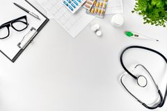 Doctor`s office desk with medical documents, charts, eyeglasses and stethoscope. Top view. Copy space. White background. Still life. Flat lay stock image