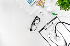 Doctor`s office desk with medical documents, charts, eyeglasses and stethoscope. Top view. Copy space stock image