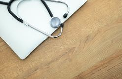 Doctor`s stethoscope and laptop computer stock images