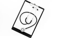 Doctor`s table. Clip pad and stethoscope on white background top view Royalty Free Stock Photography