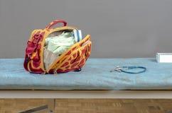 Doctor& x27; s-Tasche und -stethoskop über einer Bahre Stockfoto