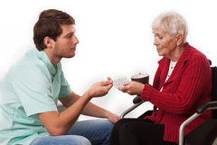 Doctor's visit at home. Doctor visiting disabled elderly women at home Royalty Free Stock Images