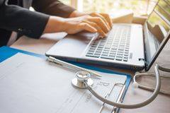 Doctor's working on laptop computer, writing prescription clipbo. Ard with record information paper folders on desk in hospital or clinic, Healthcare and medical Stock Photos
