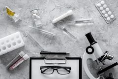 Doctor`s workplace. Microscope, tablet, pills and test tube on grey stone background top view Royalty Free Stock Photo