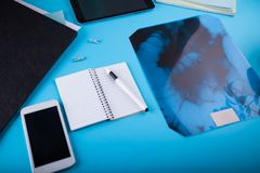 Doctor`s workspace. Roentgen image of intestines. Doctor`s workspace. Roentgen image of intestines on blue background Stock Image