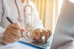 Doctor`s writing and working on laptop computer, writing prescri. Ption clipboard with record information paper folders on desk in hospital or clinic, Healthcare Stock Photography