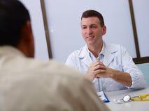 Doctor samtal till den gammala sjuka mannen i klinik Royaltyfri Bild