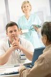 Doctor samtal till den gammalare tålmodign royaltyfri bild
