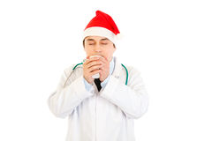 Doctor in Santa hat enjoying cup of hot coffee Royalty Free Stock Photos