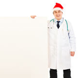 Doctor in Santa hat holding blank billboard Royalty Free Stock Photo