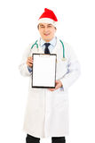 Doctor in Santa hat holding blank clipboard Stock Photography
