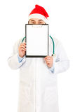 Doctor in Santa hat holding blank clipboard Stock Images