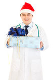 Doctor in Santa hat holding present in hands Royalty Free Stock Image
