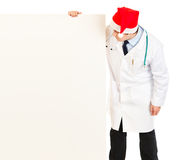 Doctor in Santa hat looking at blank billboard Royalty Free Stock Image