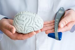 Doctor or scientist holds in one hand figure of brain in another - neurological reflex rubber hammer. Concept photo of neurology,. Neurosurgery and neuroscience royalty free stock image