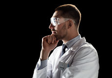 Doctor or scientist in lab coat and safety glasses. Medicine, science, healthcare and people concept - male doctor or scientist in white coat and safety glasses Royalty Free Stock Photos