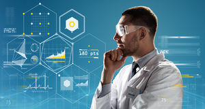 Doctor or scientist in lab coat and safety glasses. Medicine, science, healthcare and people concept - male doctor or scientist in white coat and safety glasses Royalty Free Stock Photo