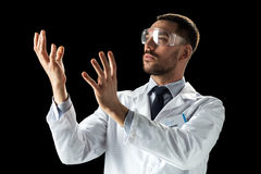 Doctor or scientist in lab coat and safety glasses. Medicine, science, healthcare and people concept - male doctor or scientist in white coat and safety glasses Stock Photo