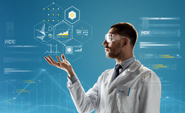 Doctor or scientist in lab coat and safety glasses. Medicine, science, healthcare and people concept - male doctor or scientist in white coat and safety glasses Stock Photos