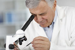 Doctor scientist looking through microscope Stock Photography