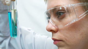 Doctor scientist looking at the test tubes in lab stock video footage