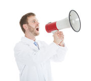 Doctor Screaming Into Megaphone. Young male doctor screaming into megaphone over white background Royalty Free Stock Image