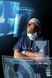 Doctor with screens. Doctor in uniform with X-rays and digital  screens and keyboard Royalty Free Stock Image