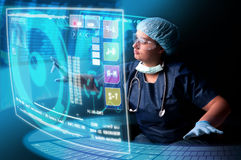 Doctor with screens. Doctor in uniform with X-rays and digital  screens and keyboard Royalty Free Stock Photos