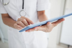 Doctor scrolling on her tablet. At work Royalty Free Stock Image