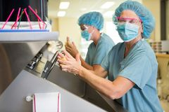 Doctor Scrubbing Hands With Colleague Royalty Free Stock Photography