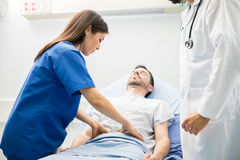 Doctor in scrubs examining a patient Stock Photo