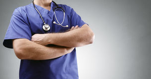 Doctor in scrubs with stethoscope. Doctor in scrubs folding arms with stethoscope and gray background for copy royalty free stock image